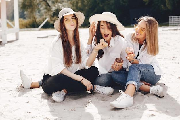 Tre belle ragazze in un parco estivo