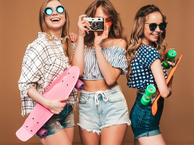 Tre belle ragazze sorridenti alla moda con skateboard penny colorati. donne in estate camicia a scacchi vestiti in posa. scattare foto con la retro macchina fotografica