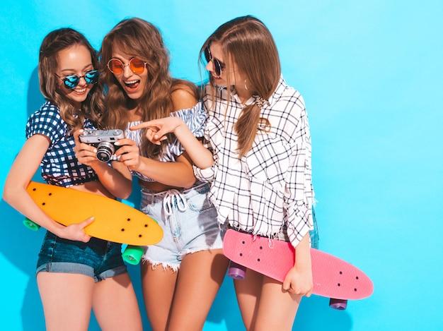 Tre belle ragazze sorridenti alla moda sexy con i pattini variopinti del penny. donne in estate camicia a scacchi vestiti in posa. modelli di scattare foto sulla fotocamera retrò