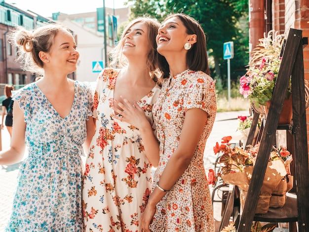 Tre belle ragazze sorridenti in prendisole alla moda estate in posa sulla strada