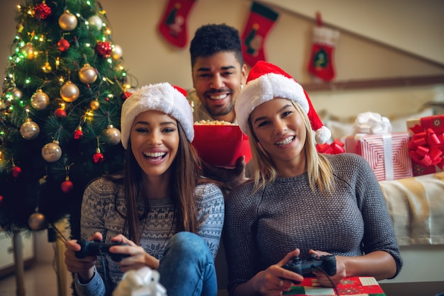 Tre bellissimi amici giocosi che si godono videogiochi e popcorn a casa per le vacanze di natale.