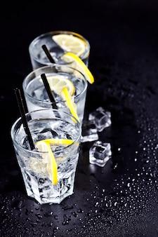 Tre bicchieri con acqua fredda gassata fresca con fette di limone e cubetti di ghiaccio