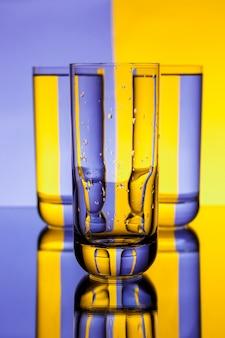 Tre bicchieri con acqua sopra il muro viola e giallo
