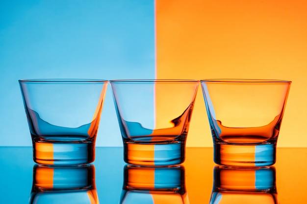 Tre bicchieri con acqua su sfondo blu e arancio.