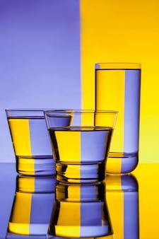 Tre bicchieri con acqua su sfondo viola e giallo.