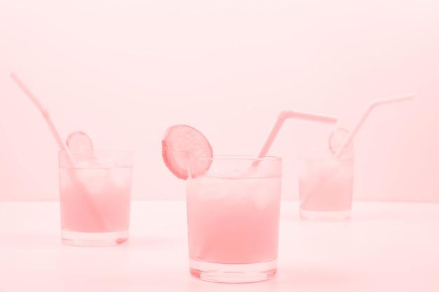 Tre bicchieri da cocktail rosa su sfondo colorato