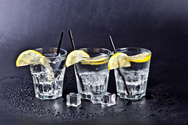 Tre bicchieri di acqua gassata fredda fresca con cubetti di ghiaccio e fette di limone