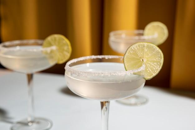 Tre bicchieri di piattino di margarita cocktail guarnito con calce sul tavolo