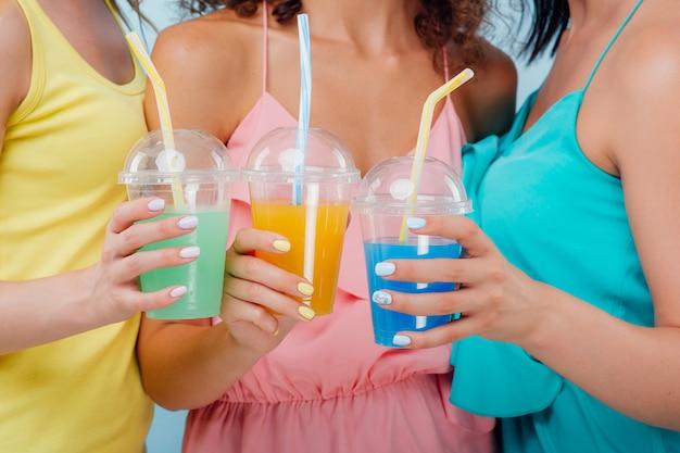 Tre bicchieri di plastica con diversi colori di succo in tre mani