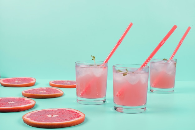 Tre bicchieri di succo di pompelmo freddo e fette sullo sfondo di menta