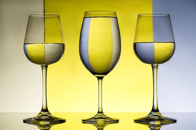 Tre bicchieri di vino con acqua su muro grigio e giallo