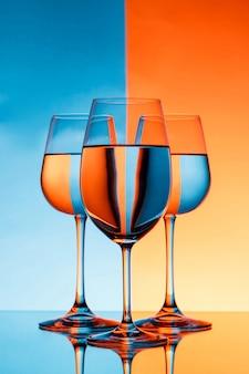 Tre bicchieri di vino con acqua sulla parete blu e arancione