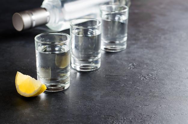 Tre bicchieri, una bottiglia di vodka, un pezzo di limone su uno sfondo scuro.