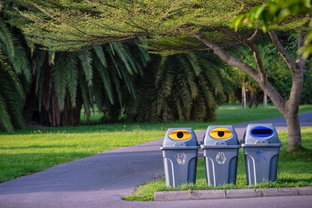 Tre bidoni della spazzatura in un parco con l'albero e le piante verdi in parco pubblico
