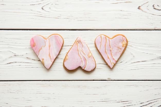 Tre biscotti a forma di cuori bianchi di marmo su fondo di legno