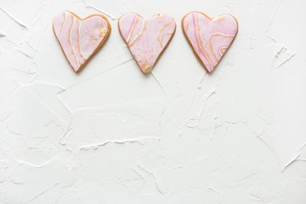Tre biscotti a forma di cuori bianchi in marmo su legno
