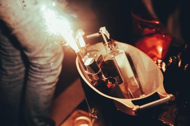 Tre bottiglie di alcool con i chiarori alla tavola della discoteca di notte nella città di barcellona.