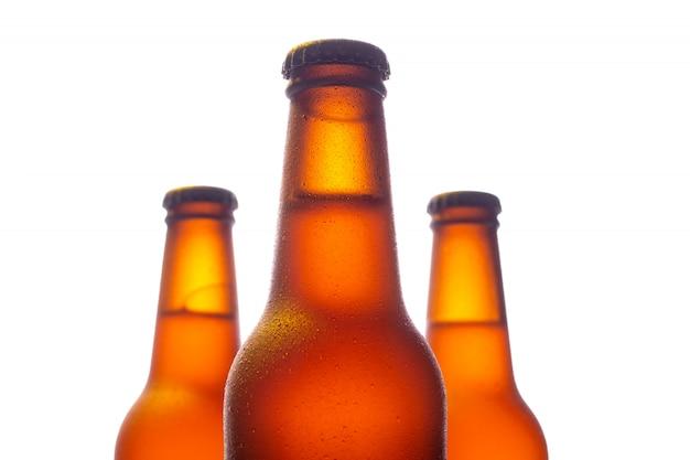 Tre bottiglie di birra fresche con piccole gocce d'acqua su bianco