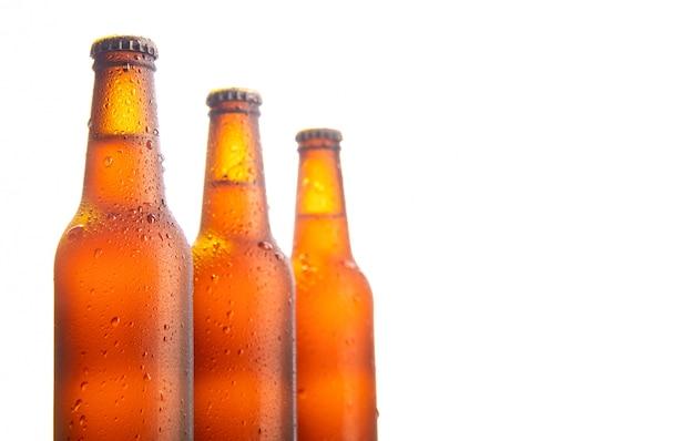 Tre bottiglie di birra fresche su bianco