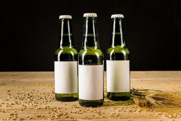 Tre bottiglie di birra verde con spighe di grano sulla superficie in legno