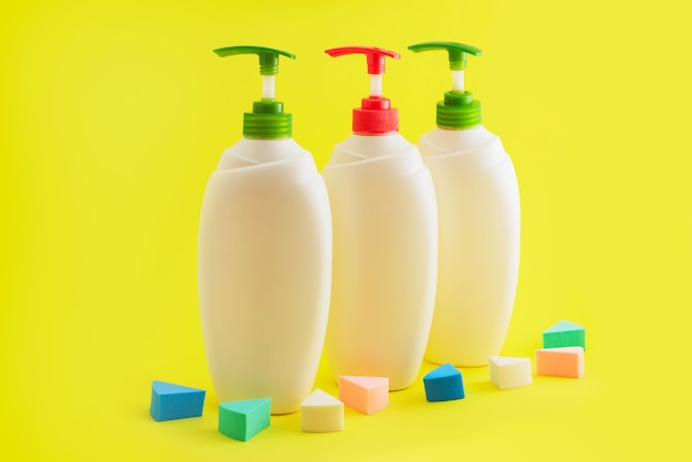 Tre bottiglie di plastica con dispenser su sfondo giallo.