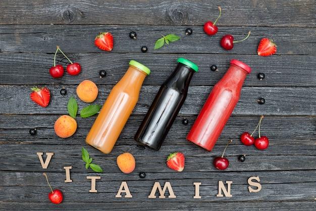 Tre bottiglie di succo di frutta, frutta e iscrizione vitamine. fondo in legno