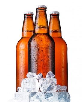Tre bottiglie marroni di birra con ghiaccio isolato