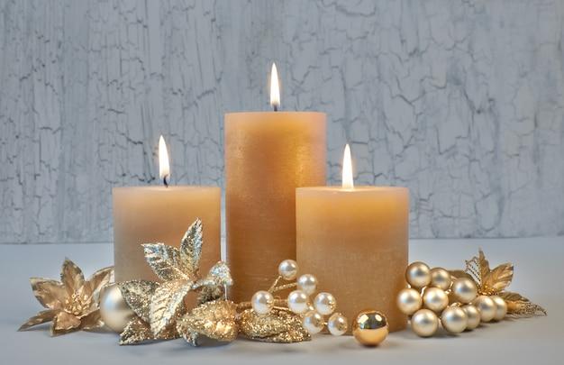 Tre candele accese con decorazioni dorate di natale