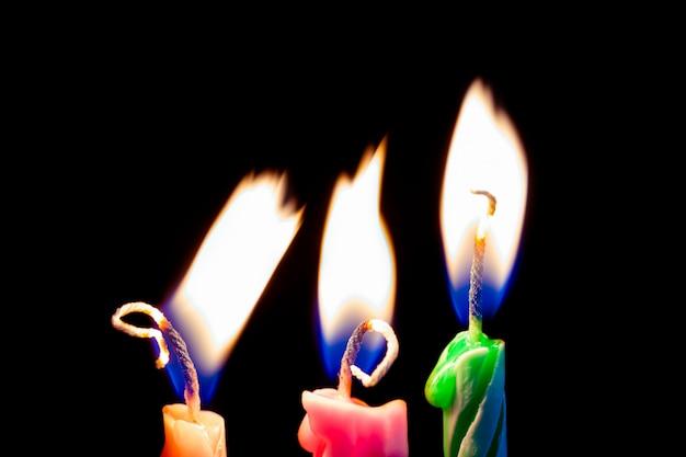 Tre candele di compleanno su sfondo nero