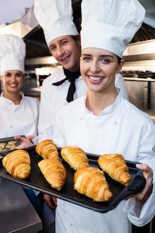 Tre chef in possesso di un vassoio di croissant e biscotti al forno