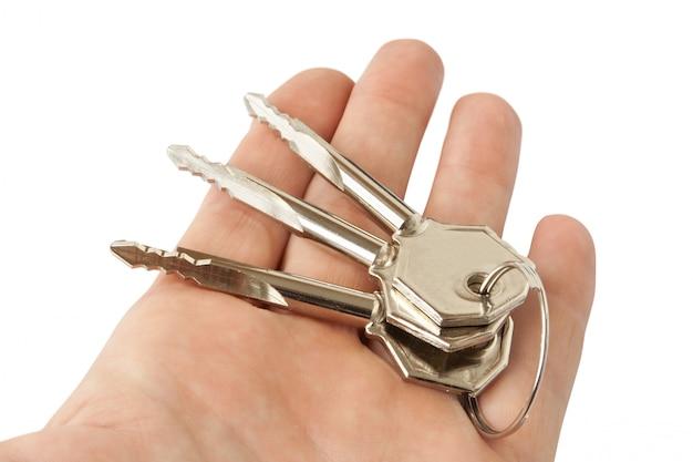 Tre chiavi nella mano isolata su bianco