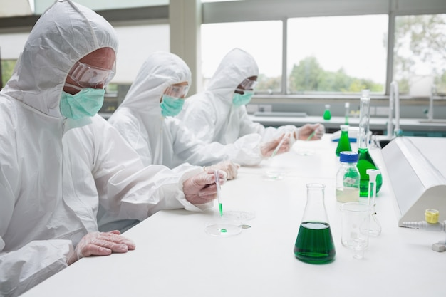 Tre chimici che lavorano in tute protettive