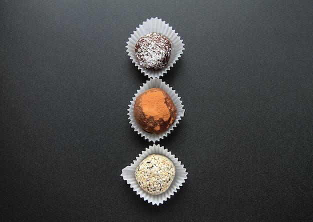 Tre cioccolatini sono su uno sfondo nero.