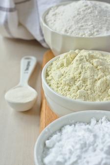 Tre ciotole con farina senza glutine - farina di riso, farina di miglio e fecola di patate e cucchiaio con gomma di xantano