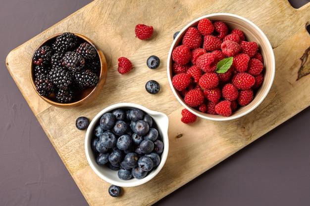 Tre ciotole con frutti di bosco, lamponi, mirtilli, more, vista zenitale