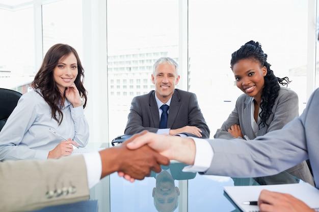 Tre colleghe sorridenti che esaminano due genti di affari che agitano le mani