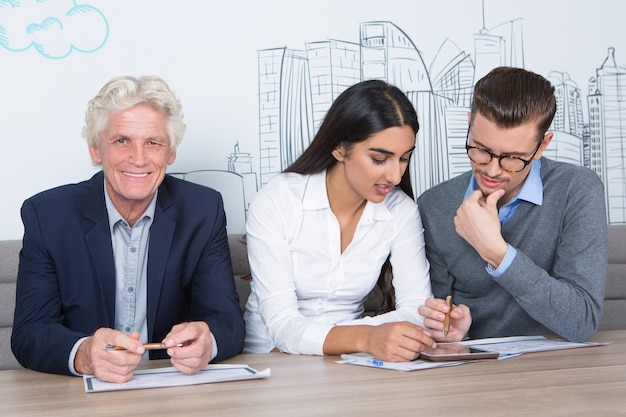 Tre colleghi di lavoro contenuti al cafe table