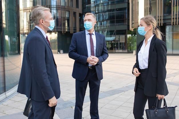 Tre colleghi di lavoro professionisti in maschere facciali discutendo affare al di fuori. contenuti manager di successo in piedi per strada e parlando di lavoro. negoziazione, protezione e concetto di partenariato