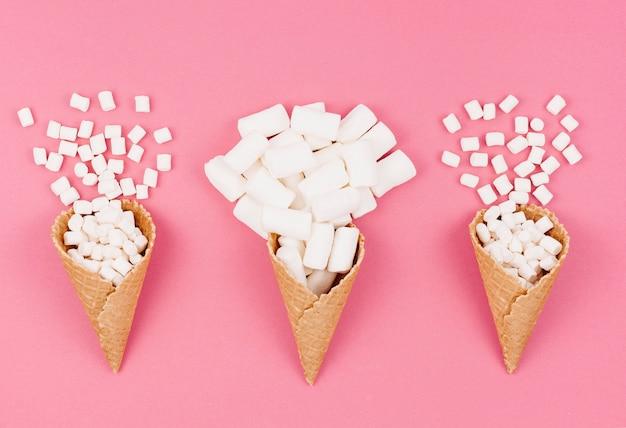 Tre coni waffle con marshmallow sul tavolo