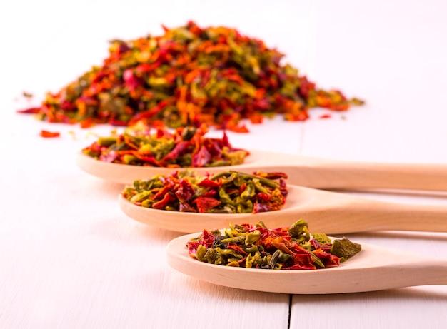 Tre cucchiai di legno con peperoni e semi secchi