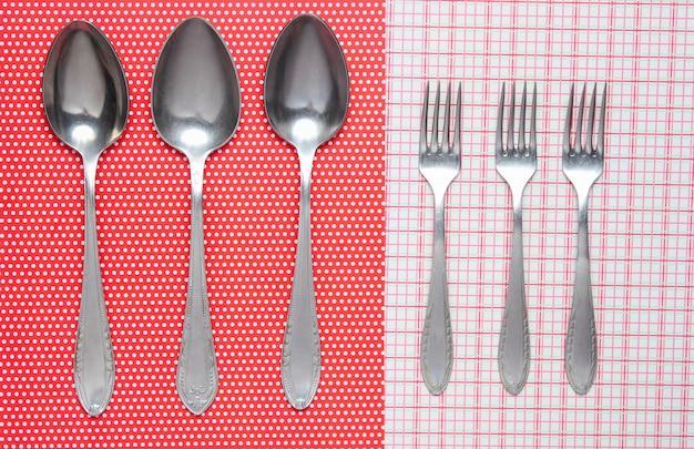 Tre cucchiai di metallo e forchette sulla tovaglia