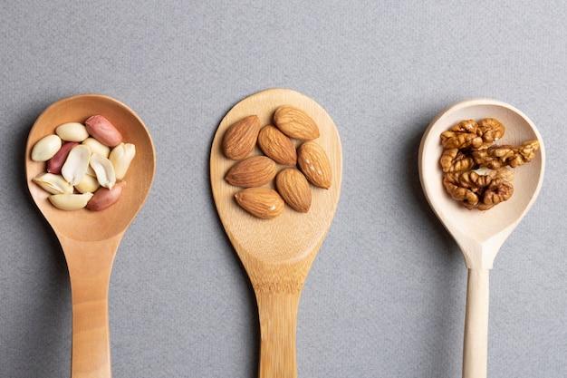 Tre cucchiaio di legno con mandorle, arachidi e noci