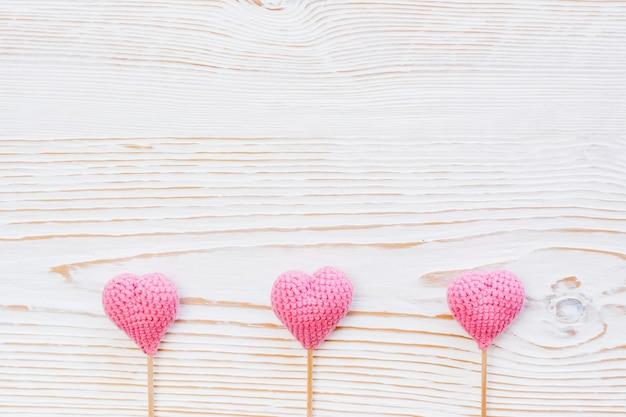 Tre cuori a maglia rosa su bastoni su un legno bianco
