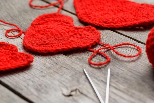 Tre cuori a maglia rossi, che simboleggiano l'amore e la famiglia. relazione familiare, legami.