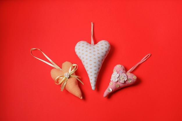 Tre cuori tessili su sfondo rosso. decorazione di san valentino in stile vintage