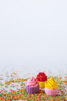 Tre cupcakes di zucchero multicolore in miniatura su sfondo chiaro con spruzza