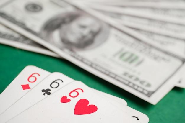 Tre di sei durante il poker con dollari sul tavolo verde.