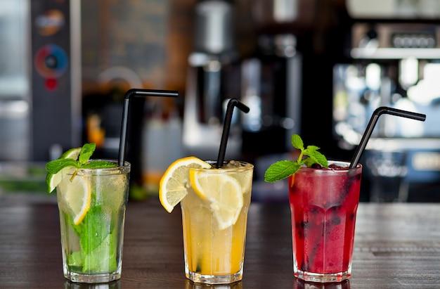 Tre diverse limonate rinfrescanti con limone e lime sulla barra del caffè. bevanda estiva