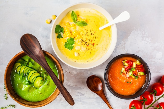 Tre diverse zuppe di crema di verdure in ciotole su zuppe di mais, cetriolo e gazpacho grigie,