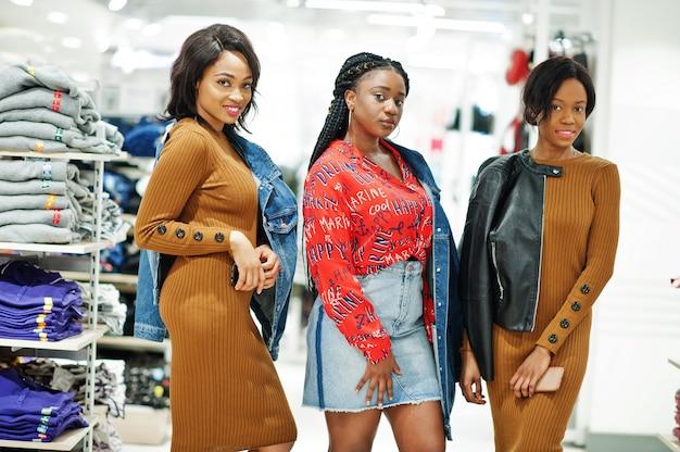 Tre donna attraente in abito marrone tunica poste al negozio di abbigliamento